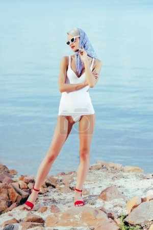 fashionable woman posing in white vintage swimwear, sunglasses and silk scarf on rocky beach