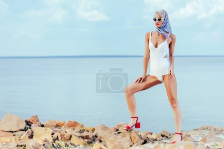 woman posing in white vintage swimsuit and silk scarf