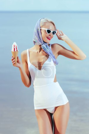 beautiful girl in vintage swimsuit, silk scarf and sunglasses holding ice cream and posing near the sea