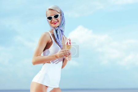 attractive smiling girl in vintage swimwear, silk scarf and trendy sunglasses holding ice cream and posing near the sea