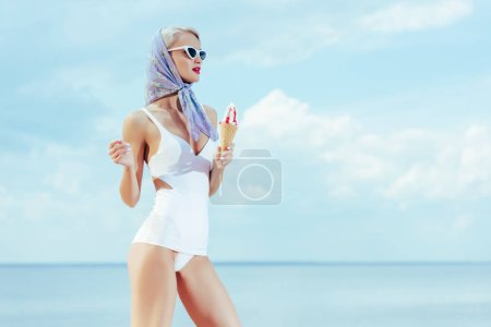 fashionable girl in stylish vintage swimsuit holding ice cream and posing near the sea