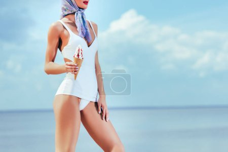 cropped view of woman in retro swimsuit holding ice cream in waffle cone