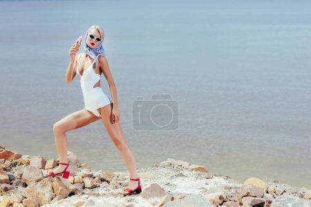 fashionable young woman in retro swimsuit posing with ice cream on rocky beach