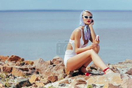beautiful woman in vintage swimwear holding ice cream and posing on rocky beach