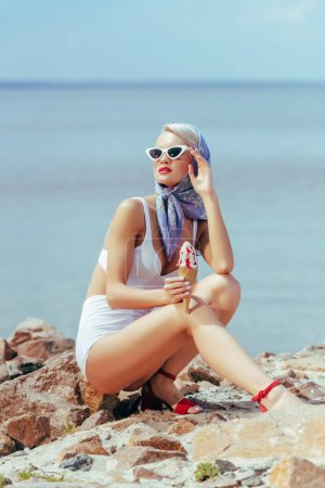 elegant woman in vintage swimsuit, silk scarf and sunglasses holding ice cream and posing on rocky beach