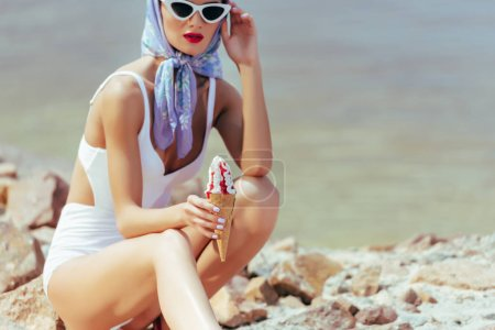 elegant young woman in vintage style posing with ice cream near the sea