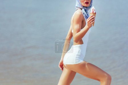 cropped view of girl in vintage white swimwear holding waffle cone with ice cream