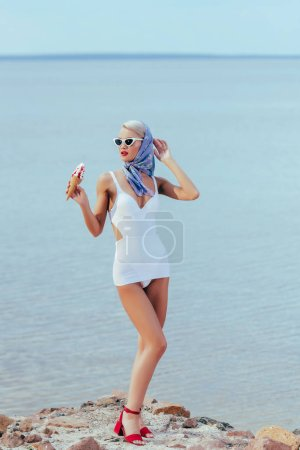 beautiful young woman in retro swimsuit holding ice cream and posing near the sea