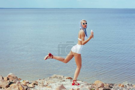 young woman in retro swimsuit holding ice cream and posing on rocky beach