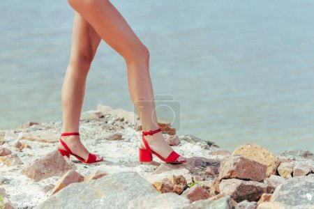 low section view of female legs in trendy red heeled sandals on rocky shore