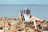 attractive girl in vintage swimsuit resting in beach chair on rocky shore