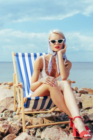 beautiful girl in stylish sunglasses relaxing in beach chair on rocky shore