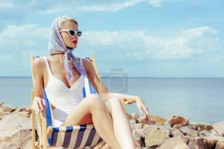 attractive stylish girl in vintage swimsuit and silk scarf relaxing in beach chair on rocky shore