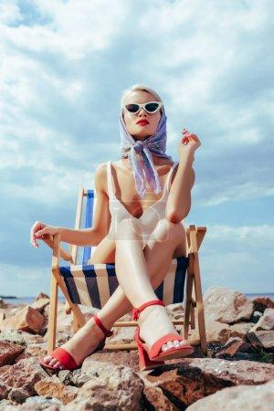 Photo pour Vue de dessous d'élégante jolie fille en maillot de bain rétro, assis dans la chaise de plage - image libre de droit