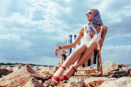 young fashionable woman in vintage swimsuit resting in beach chair on rocky shore