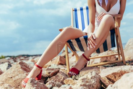 cropped view of girl in stylish swimsuit and heels sitting in beach chair on rocks