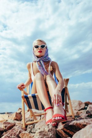 bottom view of beautiful girl in retro style relaxing in beach chair on rocky shore