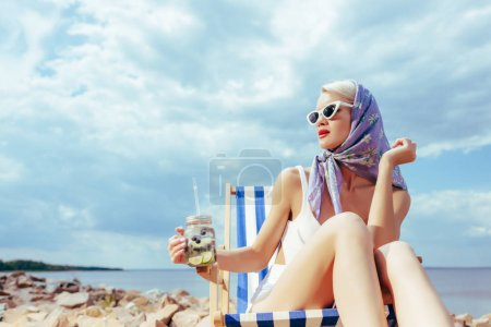 attractive fashionable girl holding lemonade and relaxing in deckchair on rocky shore