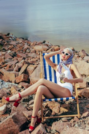 happy beautiful girl holding lemonade and resting in beach chair on rocky shore