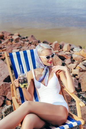 fashionable girl holding jar with lemonade and relaxing in beach chair on rocky shore