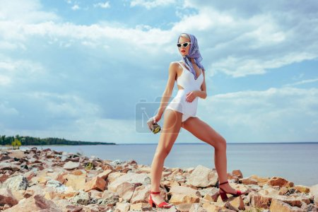 attractive girl in white vintage swimwear holding mason jar with fresh cocktail and posing on rocky beach