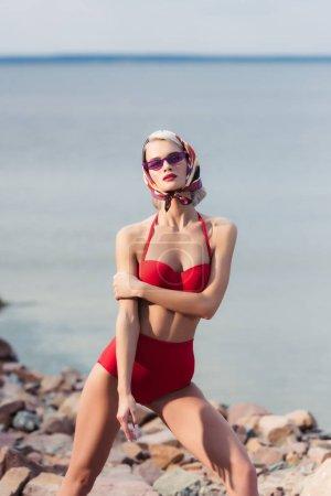 beautiful elegant woman posing in red retro bikini on rocky beach at sea