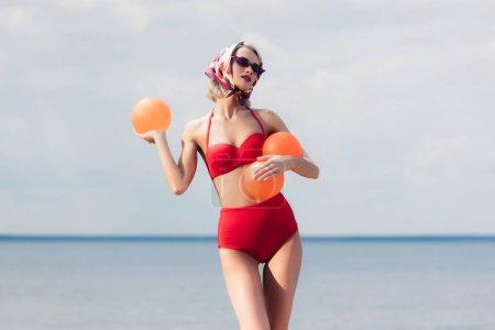 Foto de Mujer elegante atractiva en bikini rojo de moda, gafas de sol y bufanda de seda posando con las bolas en el mar - Imagen libre de derechos