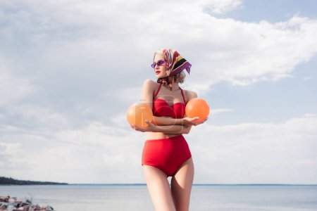 fashionable model in red bikini and silk scarf posing with balls at sea