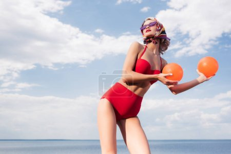 stylish model in vintage red bikini, sunglasses and silk scarf posing with balls at sea