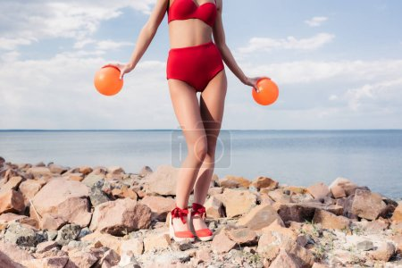 cropped view of girl in red bikini holding two balls on rocky beach
