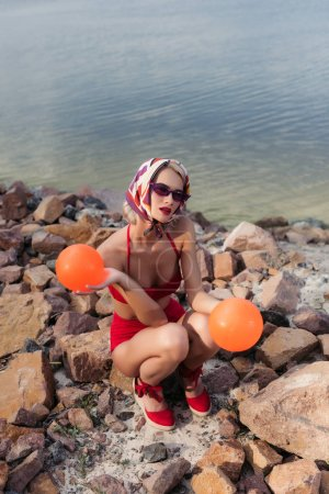 attractive slim girl in red swimwear, sunglasses and silk scarf posing with balls on rocky beach