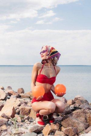 elegant woman in retro red bikini, sunglasses and silk scarf posing with balls on rocky shore