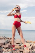 stylish woman in red bikini and silk scarf talking on yellow rotary phone and standing on shore