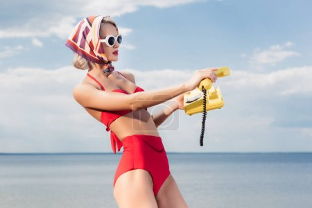 attractive woman in red bikini and silk scarf posing with yellow rotary telephone near the sea
