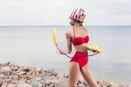 beautiful young woman in red bikini and silk scarf posing with yellow rotary telephone near the sea