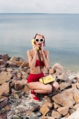 shocked girl in red bikini and silk scarf talking on vintage rotary telephone