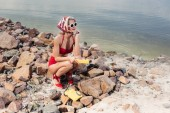 elegant girl in red bikini and silk scarf posing with rotary telephone on rocky shore