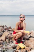 elegant woman in red bikini, sunglasses and silk scarf posing with rotary telephone