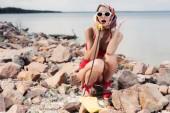 beautiful shocked woman in red bikini and silk scarf talking on vintage rotary telephone