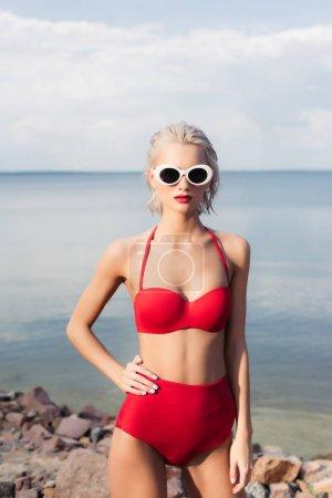 fashionable blonde girl posing in sunglasses and red bikini on rocky beach