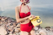 cropped view of model in red retro bikini posing with rotary telephone on rocky beach