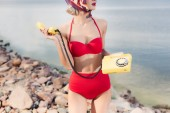 cropped view of girl in red bikini posing with rotary telephone on rocky beach
