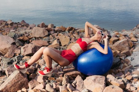 stylish girl in vintage red bikini relaxing on blue fit ball on rocky beach