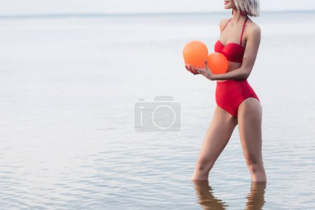 cropped view of woman in red bikini standing in water and holding orange balls