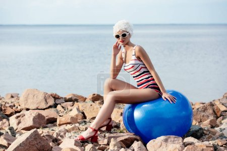 sportive girl in retro striped swimwear and sunglasses sitting on blue fit ball on rocky beach