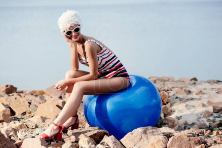 attractive girl in retro striped swimsuit sitting on blue fit ball on rocky beach