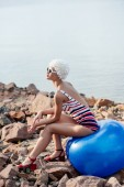 athletic woman in striped swimsuit posing on blue fitness ball on rocky beach