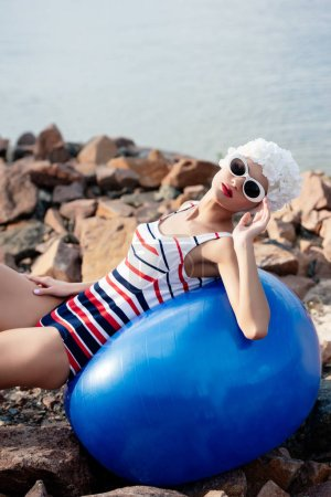 elegant woman in striped swimsuit and sunglasses lying on fitness ball on rocks