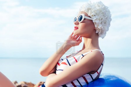 elegant woman in striped swimsuit, retro sunglasses and white hat relaxing on fit ball