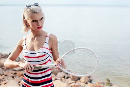 attractive blonde girl in striped swimsuit and sunglasses posing with tennis racket on beach at sea